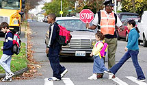 Crossing guard helping kids cross street safely