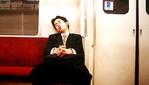 Man in suit asleep on subway train in Tokyo